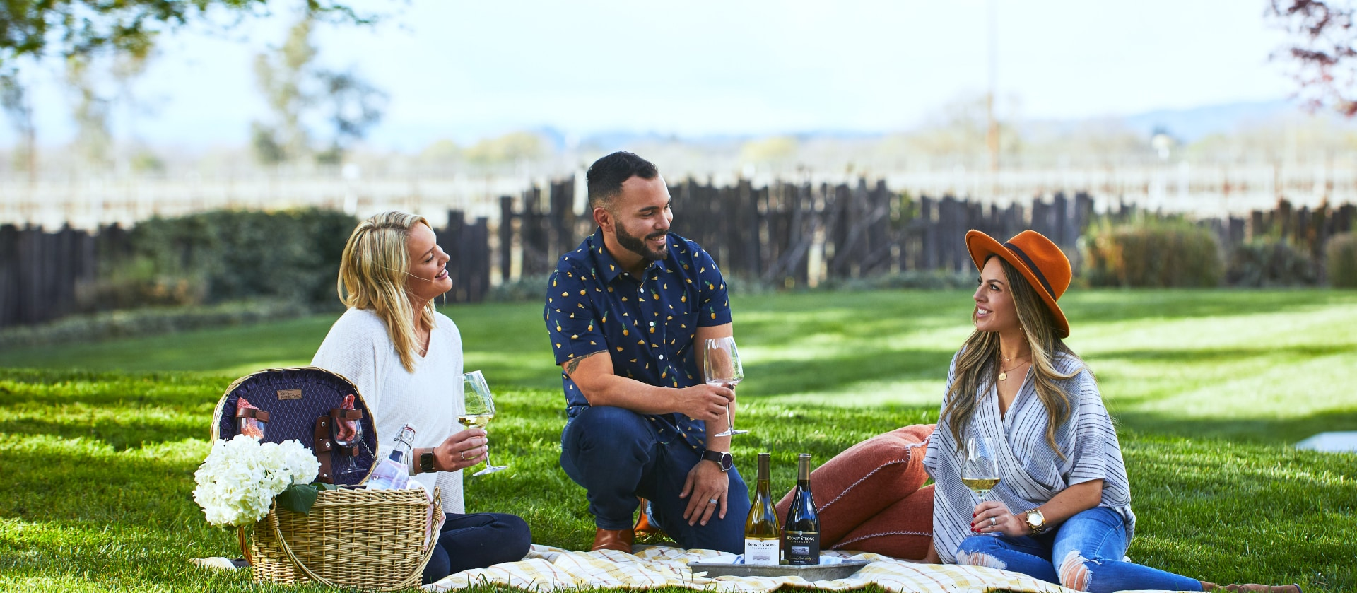 Three friends sitting on a picnic blanket enjoying wine together on the Green at Rodney Strong Vineyards tasting room