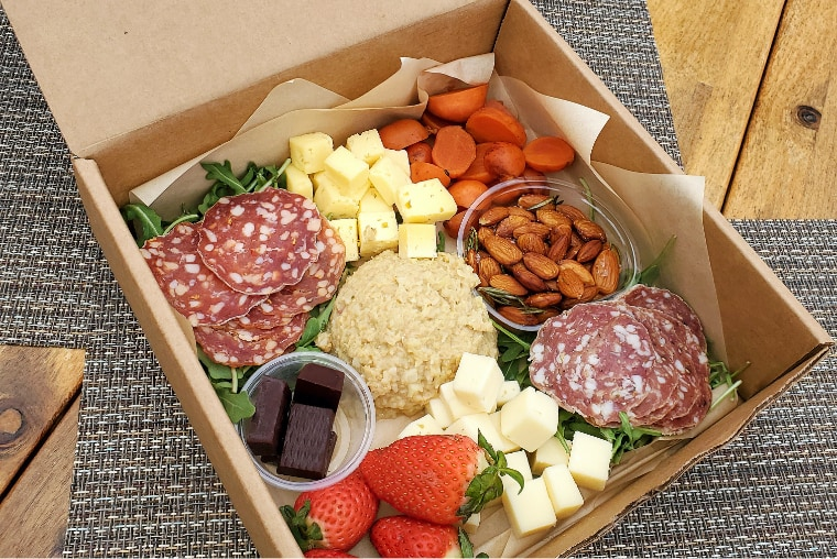 A box of assorted cheese and charcuterie beautifully displayed on a picnic table