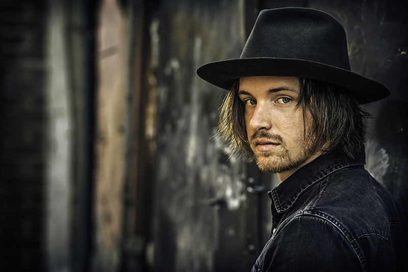 Musician David Luning in a black hat and jacket in front of a distressed wood backdrop.