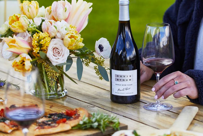 A bottle of Davis Bynum Pinot and woman's hand holding a glass of red wine while sitting at a picnic table