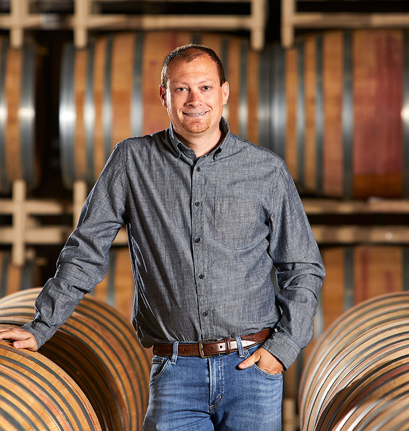 Director of Winemaking, Justin Seidenfeld, smiles in the barrel room at Rodney Strong Vineyards, resting a hand on a barrel and standing in front of a tall stack of wine barrels