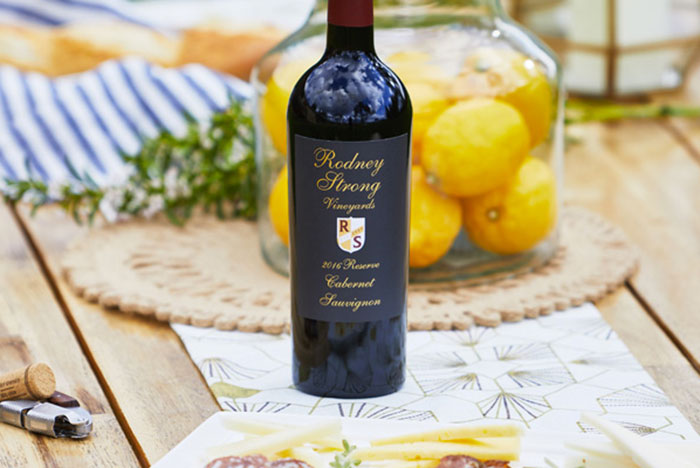 A bottle of Rodney Strong Reserve Cabernet on a picnic table set with a vase of lemons and picnic accessories