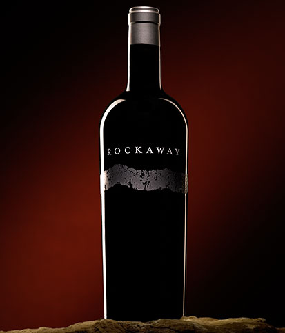 A single bottle of single vineyard Cabernet against a shadowed red background