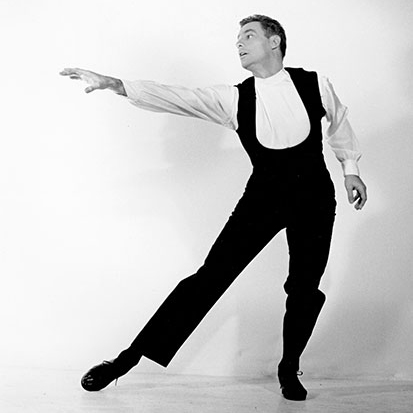 A young Rod Strong holds a dance pose while wearing dance clothes in front of a white backdrop
