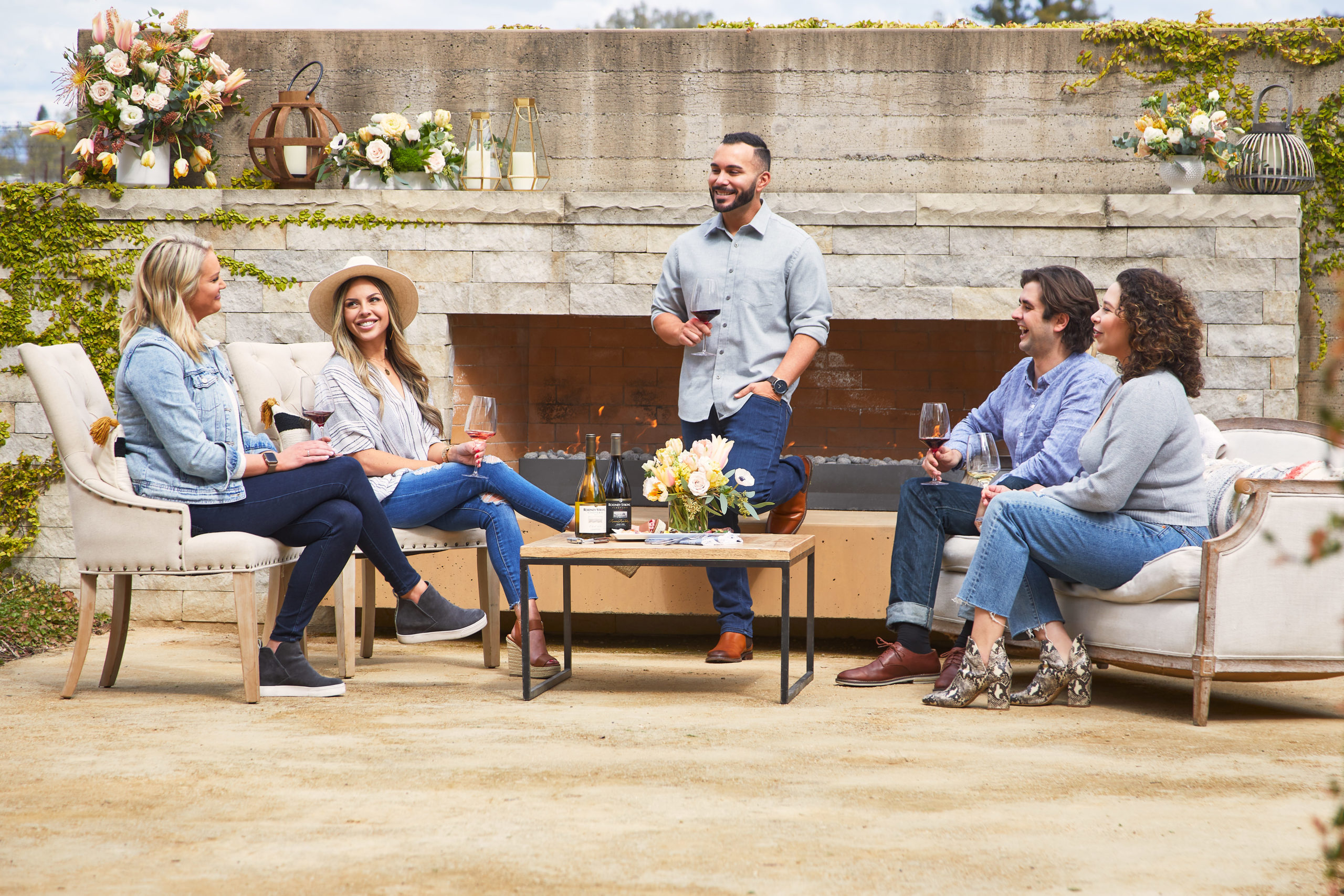 A group of friends enjoying wine in front of an outdoor fireplace in the afternoon