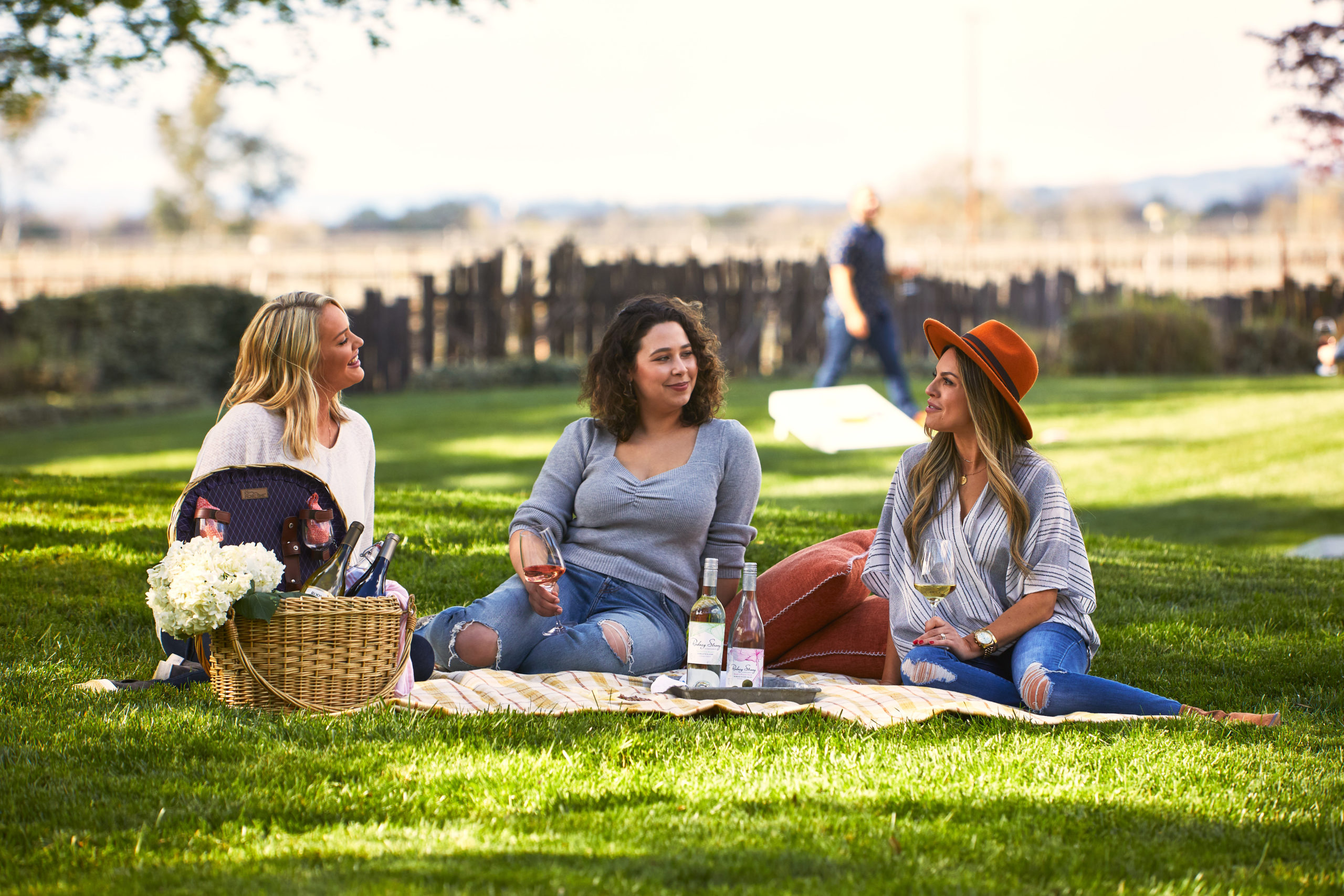 Three women relax with wine and a picnic basket on a blanket in the middle of a lush green lawn with a fence and trees in the distance